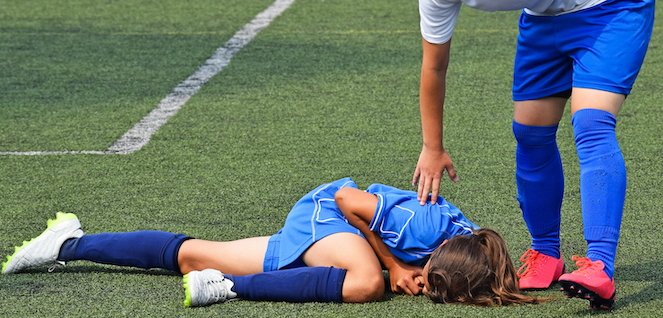Injured soccer player on ground with help arriving