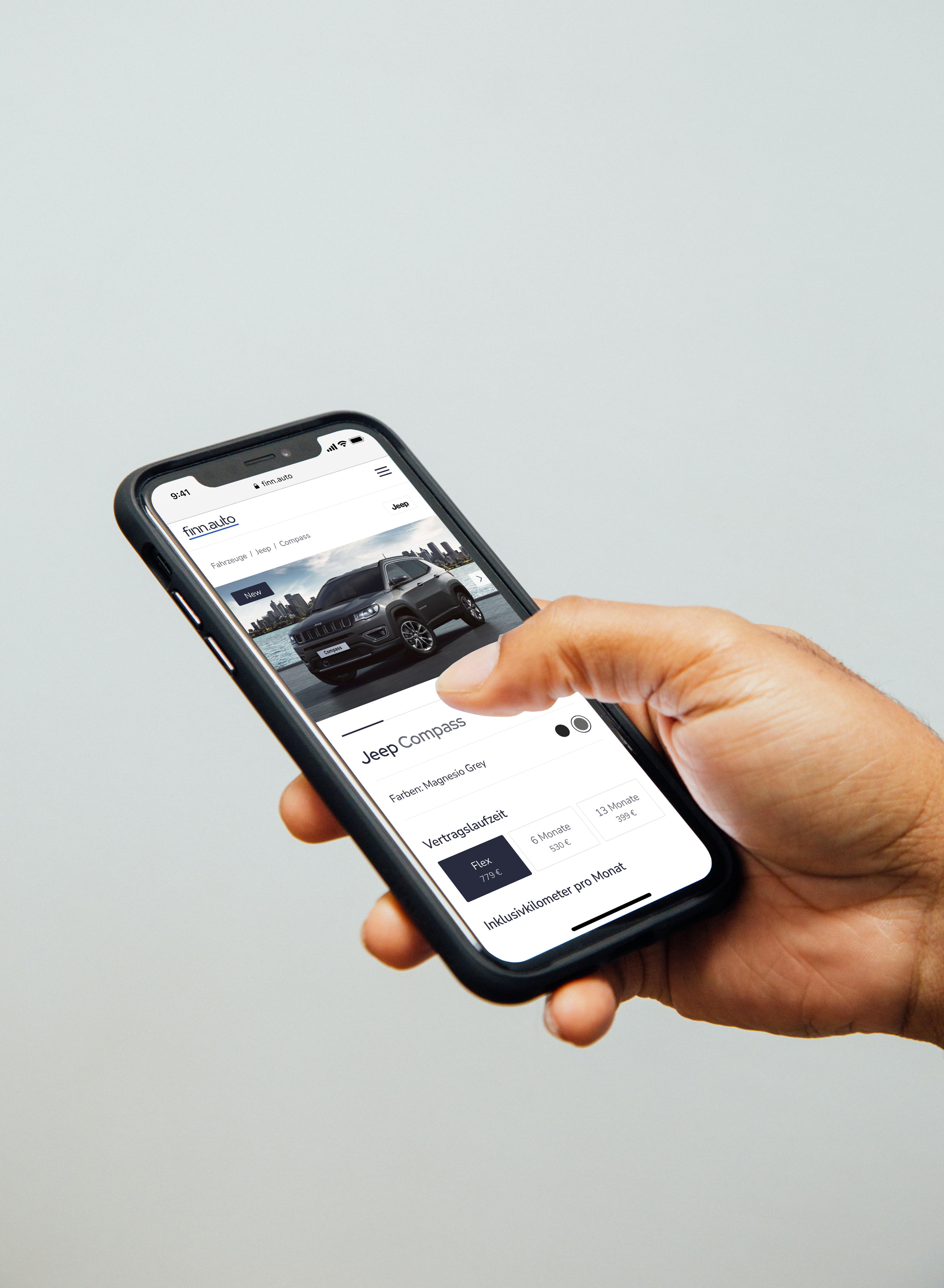 Hand hält ein Smartphone, auf dem die Website finn.auto angezeigt wird