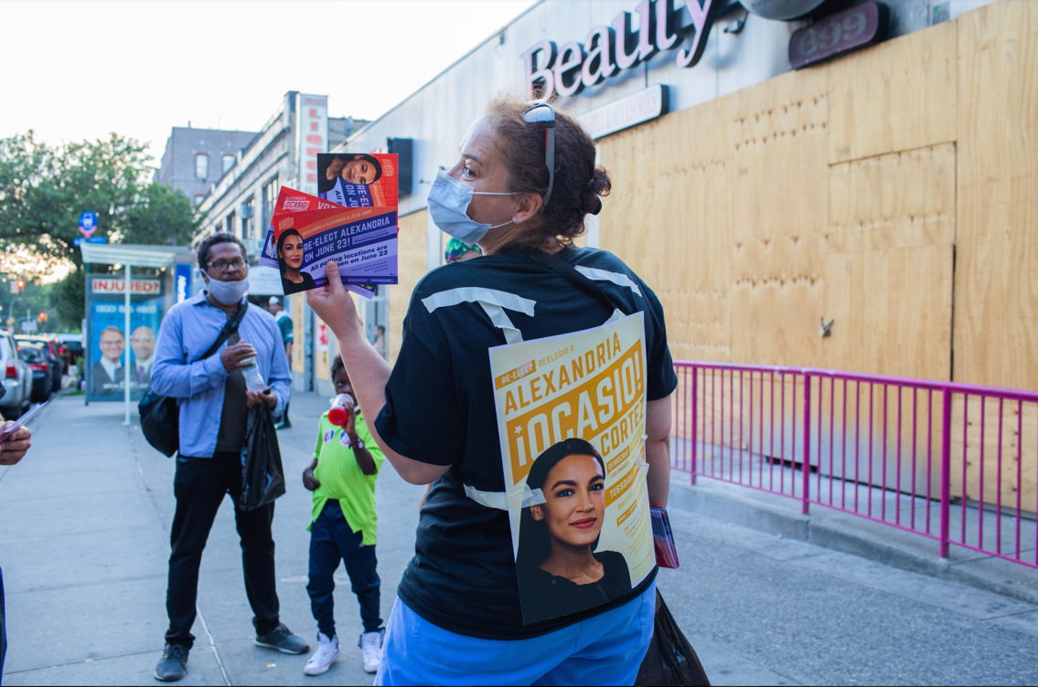Volunteer with AOC poster on their back handing out postcards