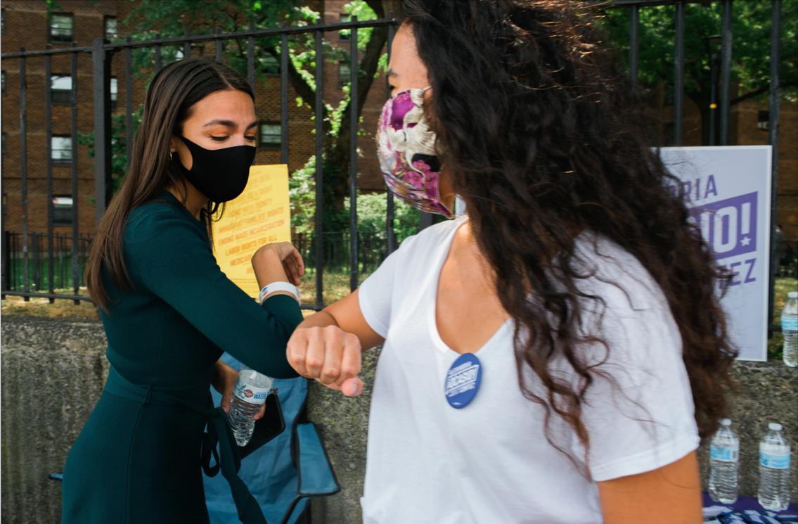 Alexandria Ocasio-Cortez bumping an elbow with a volunteer