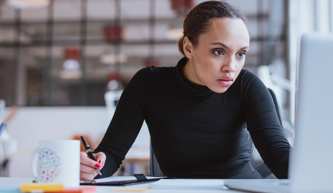 Woman looking at computer with pen in hand wearing black shirt
