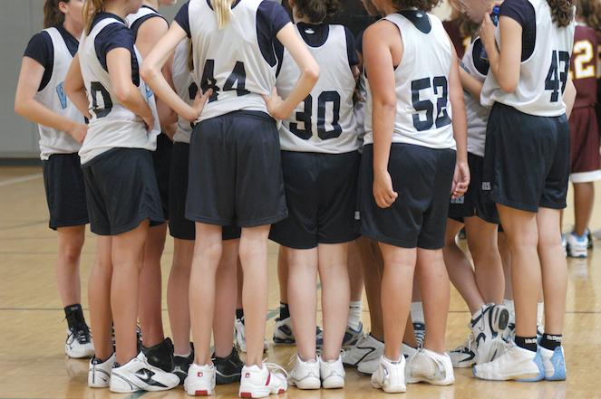 Female team huddle with backs to camera wearing white jerseys