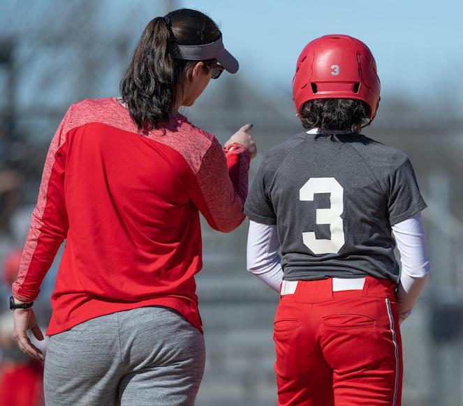 Softball coach coaching player
