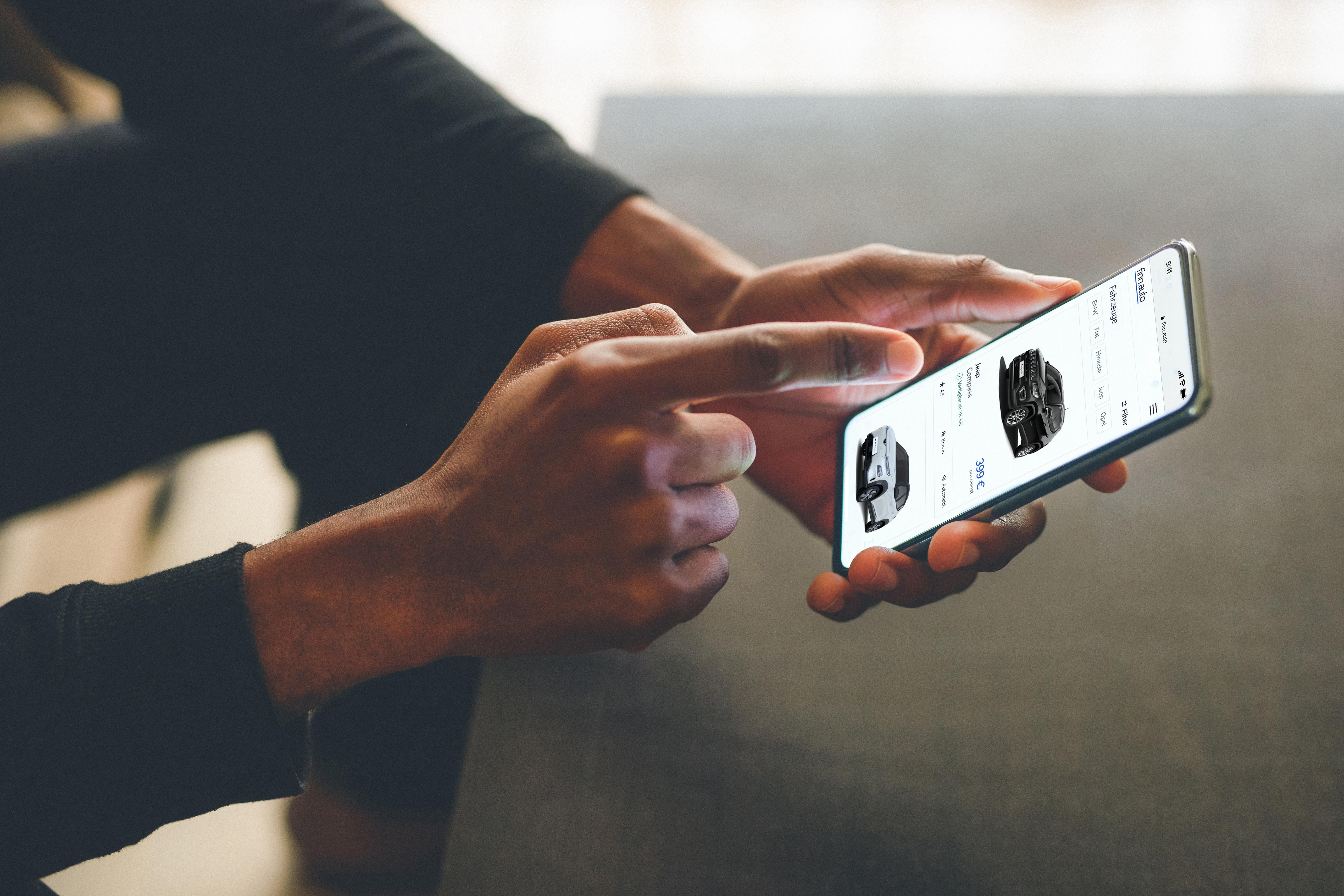 Person zeigt auf ein Smartphone, auf dem die Website finn.auto angezeigt wird