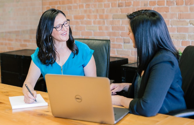Two women professionals chatting in front of a laptop at an office