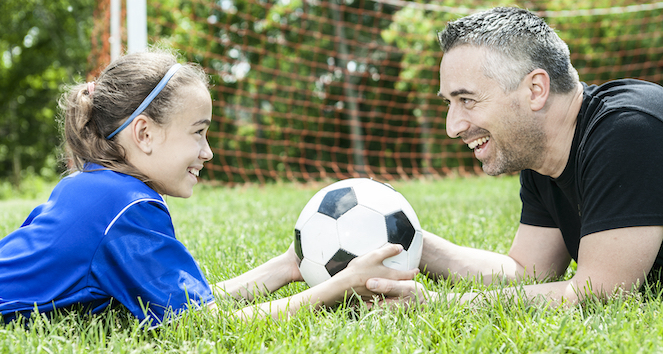 Dad and daughter laying in grass holding soccer ball