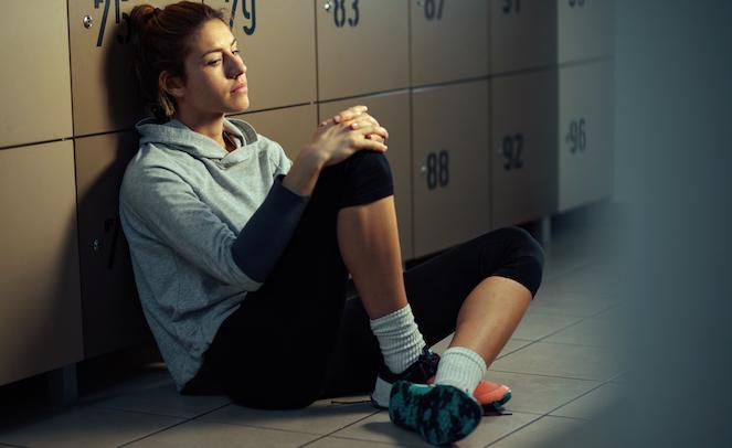 Female sitting on floor of locker room with hands on knees looking sad