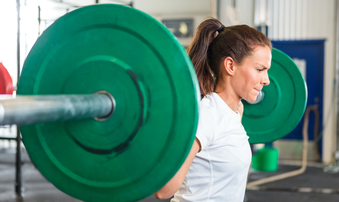 Female squatting with green weights at gym