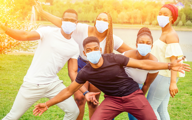 Family outside with masks posing for picture